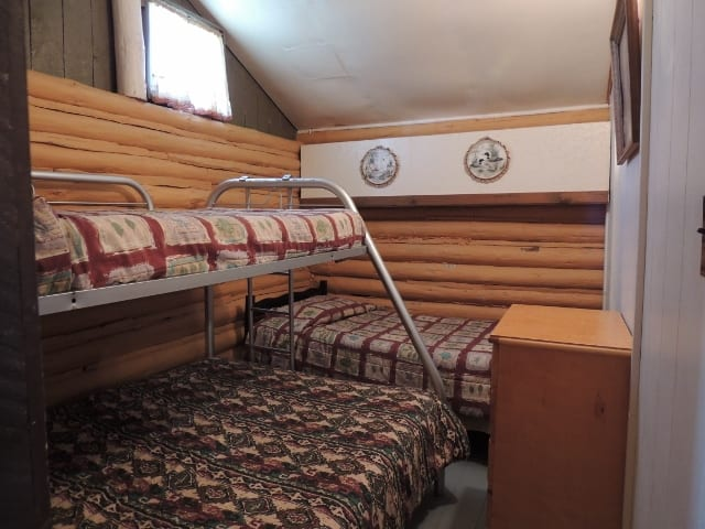 Cabin bedroom with bunkbed and twin bed.