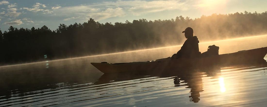 Kayaker on lake at sunrise.