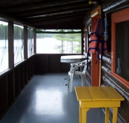 Cabin 1 enclosed patio with table and chairs.