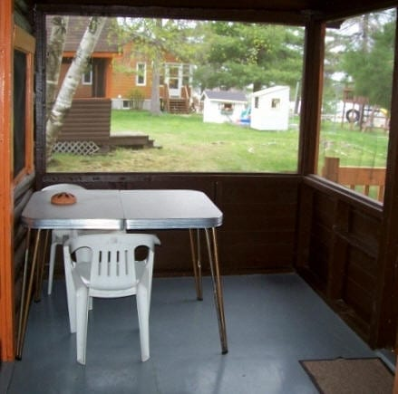 Cabin enclosed patio with table and chairs.