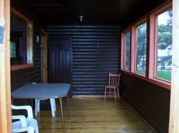 Cabin enclosed patio with chairs and table.