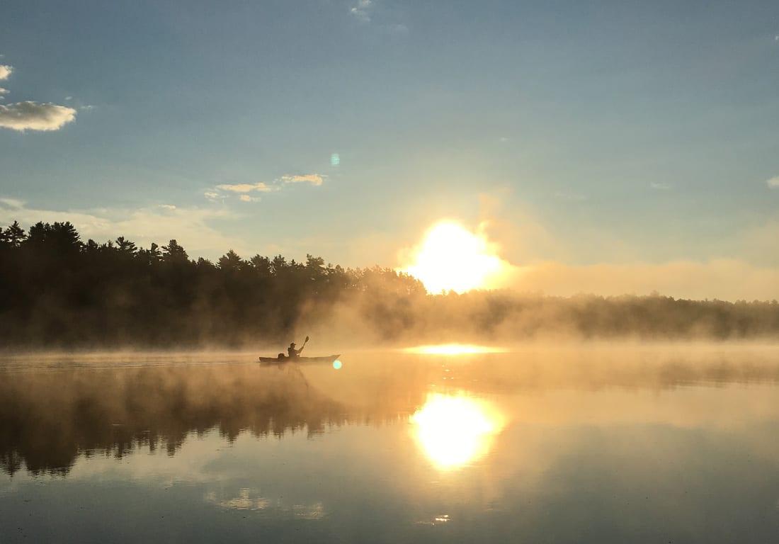 Kayaker on lake at sunset.