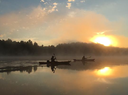 Kayakers on lake at sunrise.