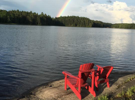 Adirondack chairs on lake shore.